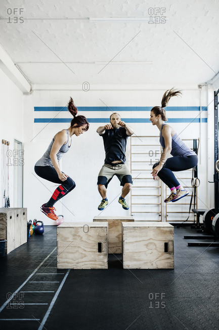 Germany, Young women and man jumping in gym