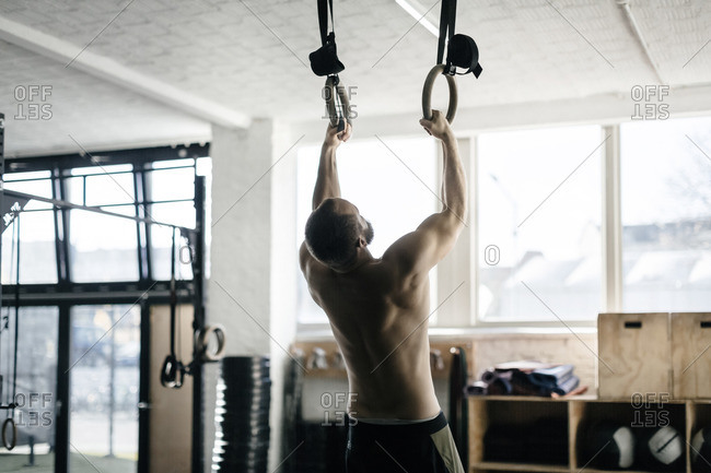 Germany, Young man training on gymnastic rings