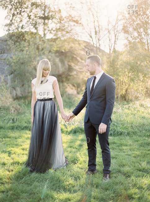 Sweden, Bride and groom standing on grass, holding hands
