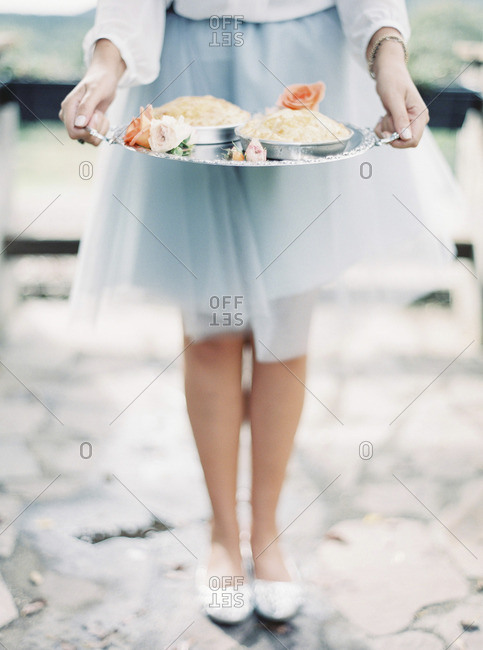 Italy, Woman in elegant skirt holding silver tray with dessert