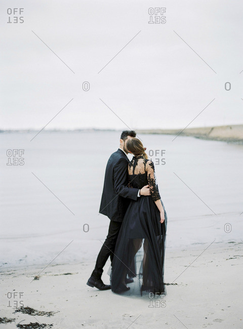 Sweden, Holland, Varberg, Young formally dressed couple walking along beach