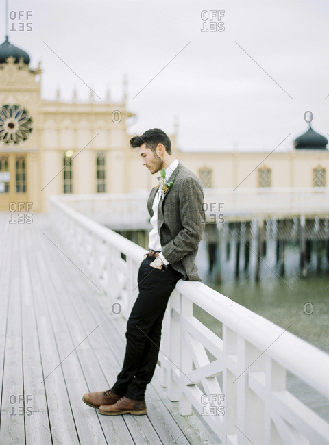 Sweden, Holland, Varberg, Groom wearing tuxedo leaning against railing on pier