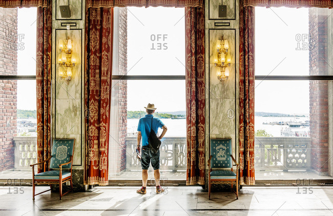 Norway, Oslo, Oslo City Hall, Tourist looking through window