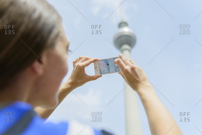 Alexanderplatz, Berlin, Germany - July 14, 2014: Germany, Berlin, Alexanderplatz, Woman photographing television tower