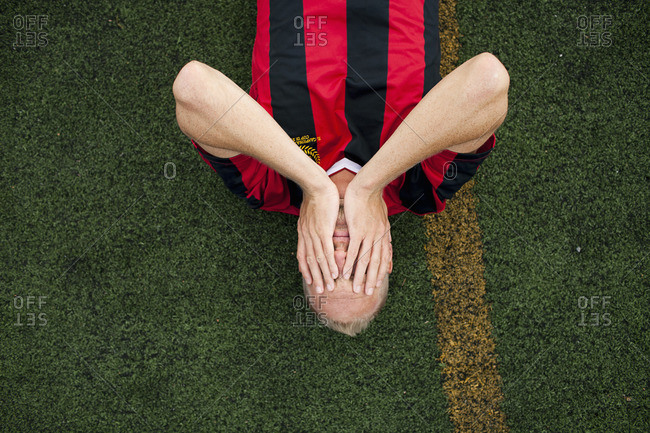 Sweden, Soccer player lying down on soccer field, head in hands