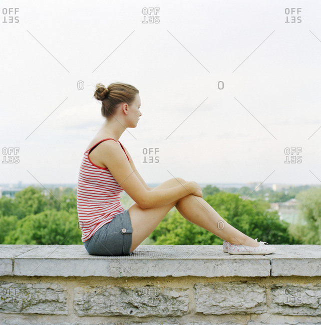 Estonia, Tallinn, Side view of young woman sitting on surrounding wall and looking at view