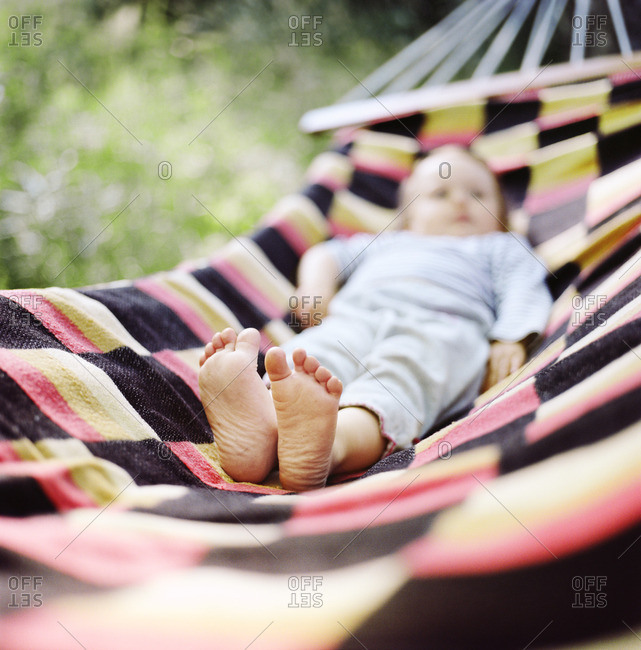 Finland, Uusimaa, Lapinjarvi, Baby girl lying on hammock, focus on bare feet