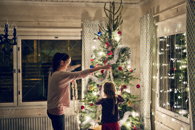 Finland, Mother with daughter decorating christmas tree
