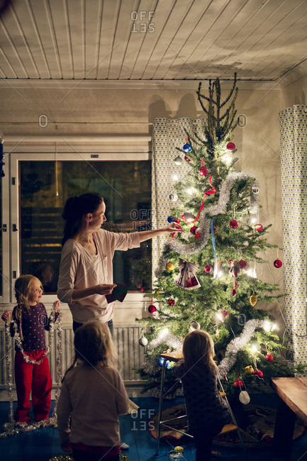Finland, Mother with daughters (12-17 months, 2-3, 4-5) decorating christmas tree