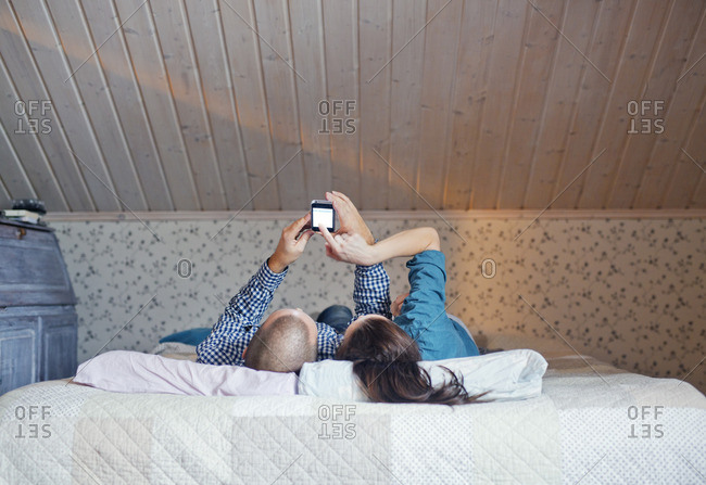 Finland, Couple lying on bed and using smart phone