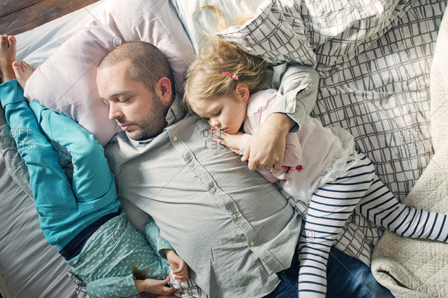 Finland, Father sleeping with daughters (12-17 months, 2-3) on bed