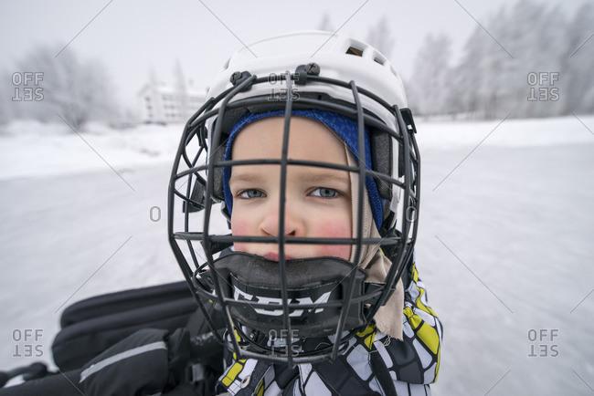 Finland, Pohjois-Pohjanmaa, Oulu, Portrait of boy in ice hockey helmet