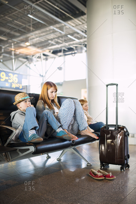 Finland, Helsinki, Helsinki Airport, Woman with boys sitting with luggage at airport