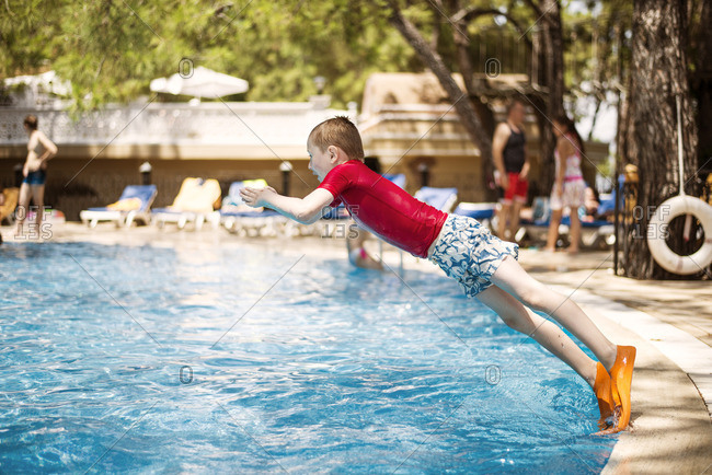 Turkey, Mugla, Marmaris, Boy wearing diving slippers jumping into swimming pool at holiday resort