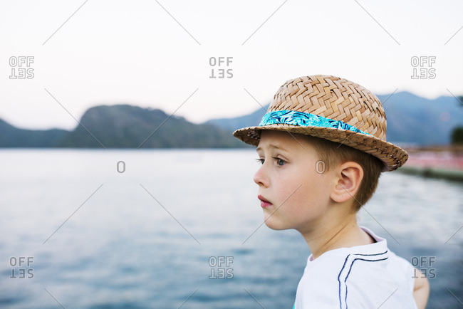 Turkey, Mugla, Marmaris, Portrait of boy in sunhat looking away from camera, sea and mountains in background