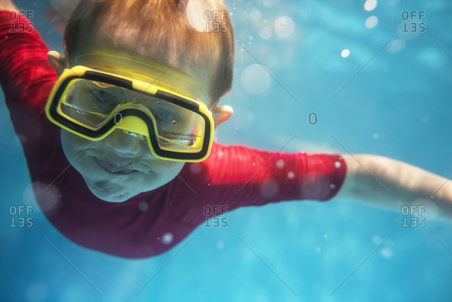 Turkey, Mugla, Marmaris, Boy diving underwater in outdoor swimming pool with swimming goggles