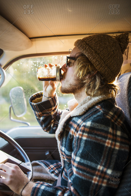 Australia, Queensland, Side view of driver drinking coffee in car