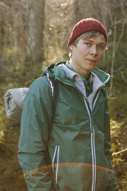 Finland, Esbo, Kvarntrask, Portrait of young man wearing woolly hat and windcheater jacket in forest