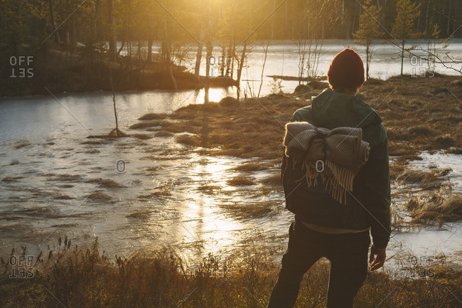 Finland, Esbo, Kvarntrask, Young man standing on marshy lakeshore
