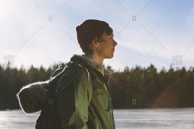 Finland, Esbo, Kvarntrask, Portrait of young man on shore of forest lake