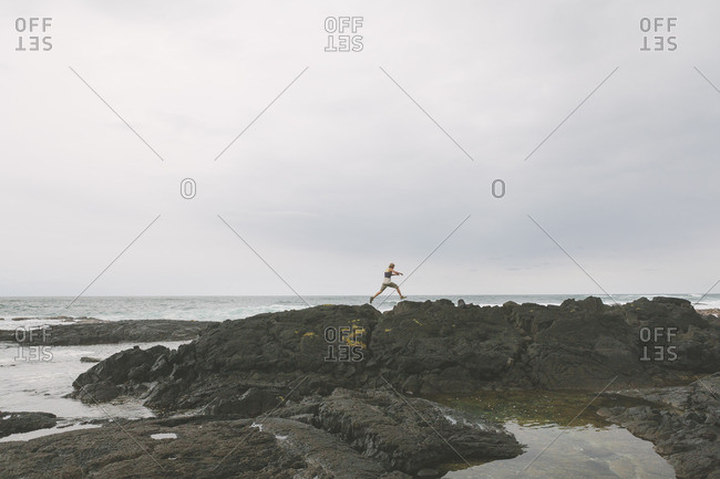 USA, Hawaii, Big Island, Man jumping over cleft in rock formation on seashore