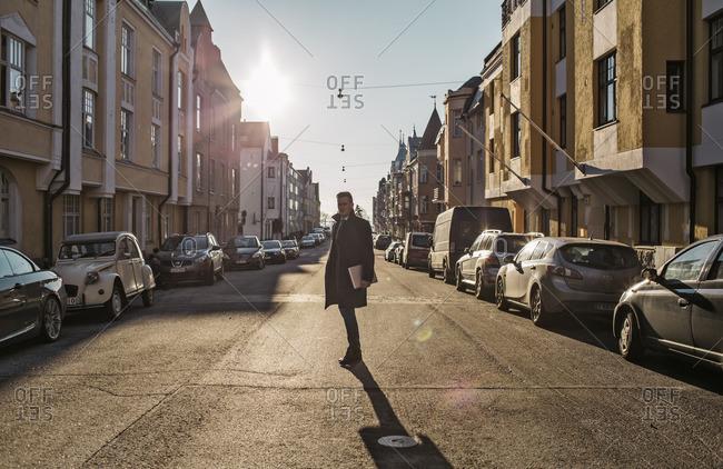 Helsinki, Finland - November 12, 2014: Finland, Helsinki, Man standing in sunlit street
