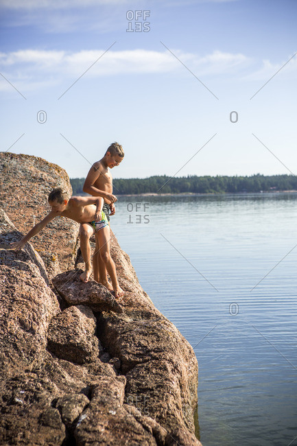 Finland, Uusimaa, Baltic Sea, Porvoo, Boys in swimwear on rock above sea