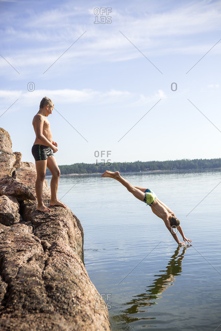 Finland, Uusimaa, Baltic Sea, Porvoo, Boys jumping into water from rock