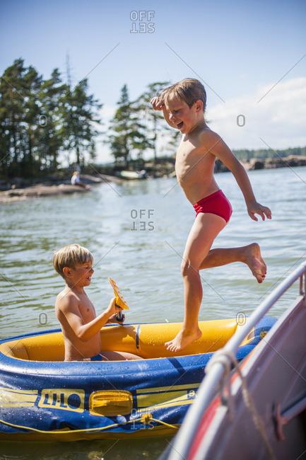 Finland, Paiijat-Hame, Konnivesi, Boys playing in inflatable raft