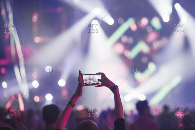 Finland, Uusimaa, Helsinki, Woman using smart phone on concert