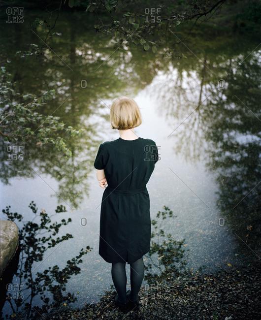 Finland, Varsinais-Suomi, Young woman standing at edge of lake