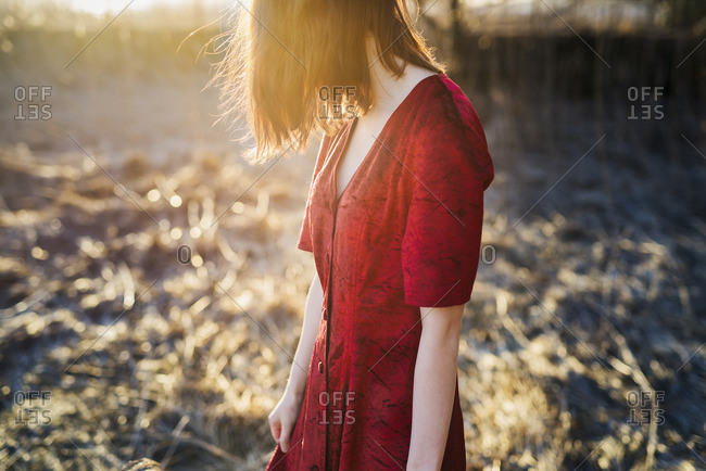 Finland, Varsinais-Suomi, Young red hair woman in red dress standing in sunlight