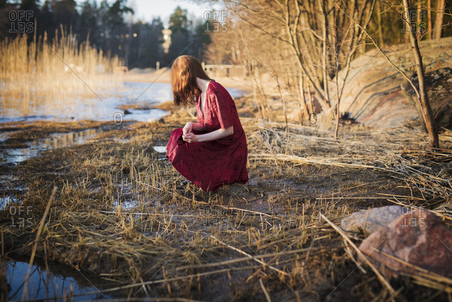 Finland, Varsinais-Suomi, Young woman crouching in wetlands
