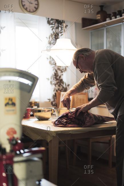 Finland, Pirkanmaa, Butcher preparing venison meat