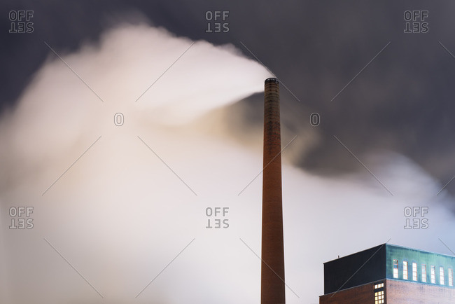 Finland, Pirkanmaa, Smoke coming out of smoke stack at night