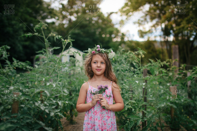 Young girl standing outside in a garden holding wildflowers and wearing a flower crown