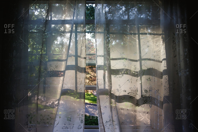 Shadows from an open window visible on lace curtains