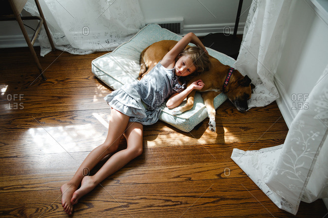 Young girl lying down on the floor with her dog