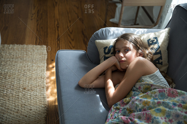 Young girl lying down on a couch