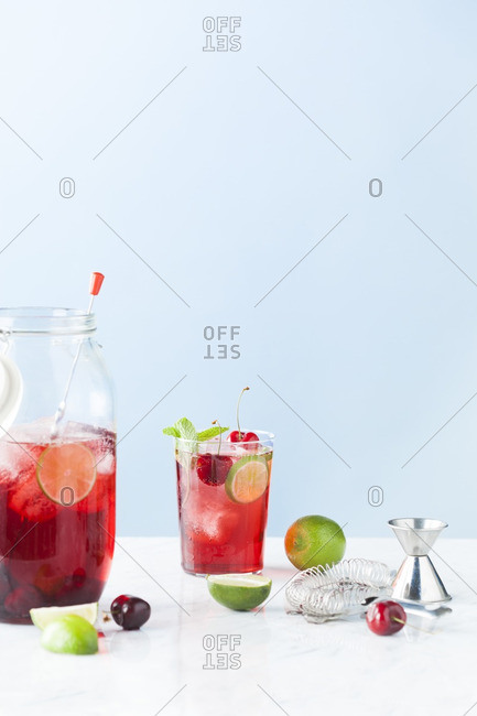 Pitcher and glass of cherry lime mojito cocktail