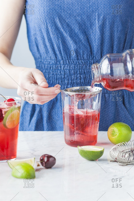 Woman making a cherry lime mojito cocktail