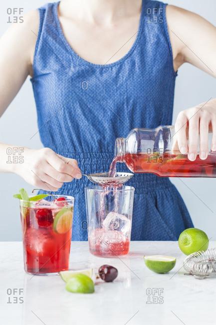 Woman preparing a cherry lime mojito cocktail