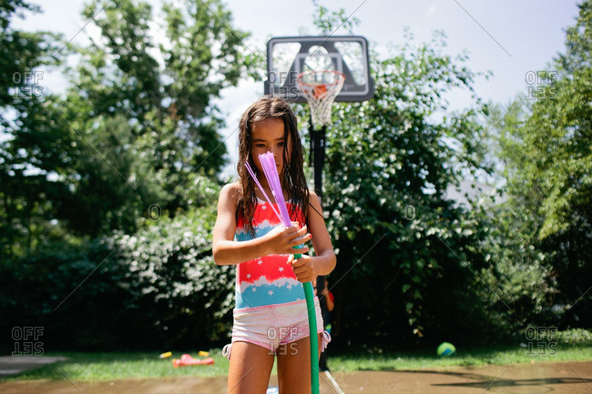 Young girl standing outside holding a water hose