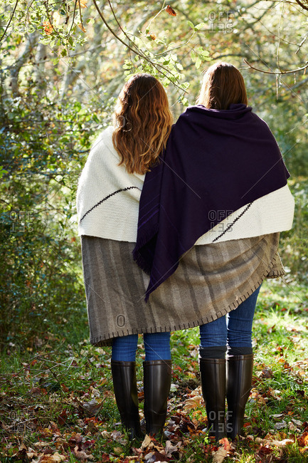 Two women standing together in the woods sharing a blanket