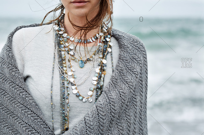 Close-up of a woman standing along a beach wearing a necklace and a shawl