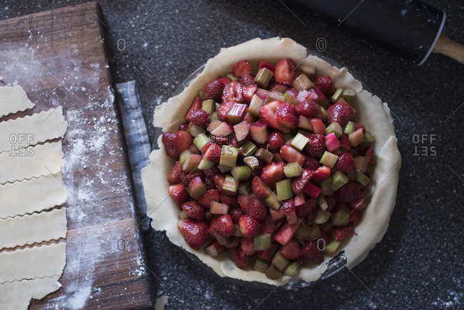 Strawberry rhubarb pie and pie dough on a wood cutting board