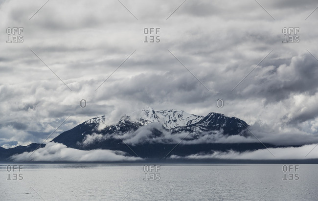 Clouds surrounding a snow covered mountain range