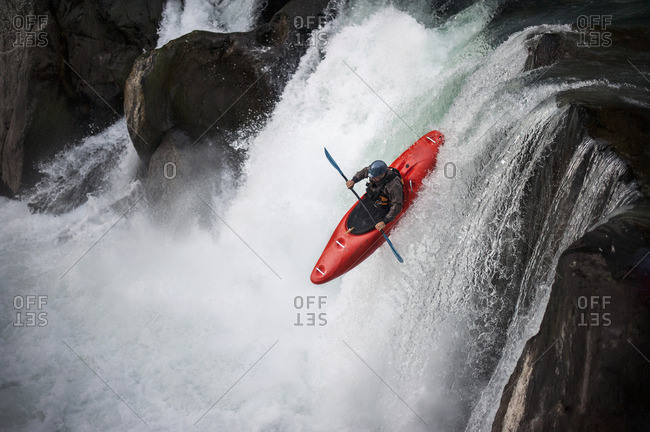 Man kayaking down a waterfall