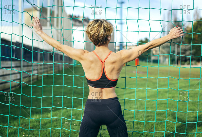 Athletic woman holding onto a net