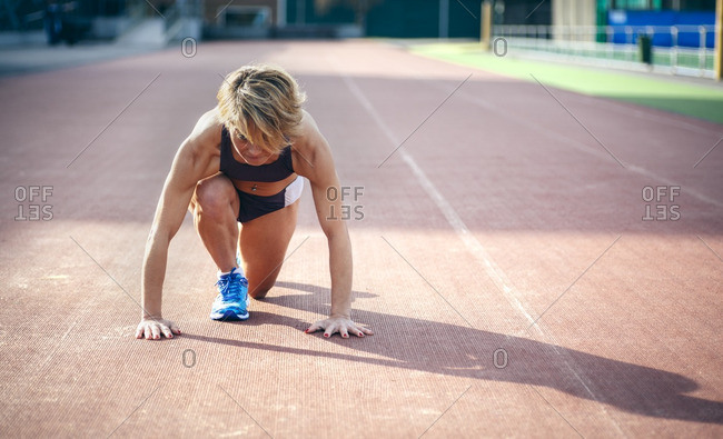 Athletic woman kneeling on a race track